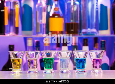 Big row of shots glasses with color drinks - Stock Photo