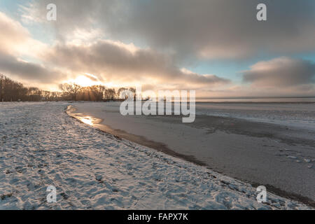 Winter evening on the bank of the lake with the first ice and snow. - Stock Photo