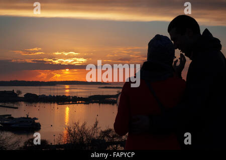 Lovers in Kaivopuisto park at sunset, Helsinki, Finland. The sunsets from the southern part of Helsinki in Kaivopuisto - Stock Photo