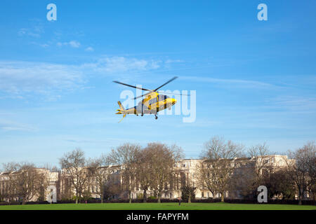 Airborne yellow and black police helicopter hovering over Regent's Park, London, UK - Stock Photo