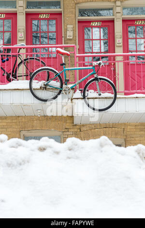 Typical facade of a condominium in Montreal, with a hanging bike covered with snow, in Winter - Stock Photo