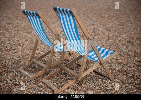 Blue-and-white striped deckchairs on Brighton Beach. - Stock Photo