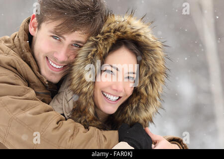 Couple smiling with perfect teeth hugging and looking at camera in winter in a forest - Stock Photo