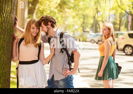 Jealous girl looking at flirting couple outdoor. Happy young woman and man couple dating. Summer romance affair. - Stock Photo