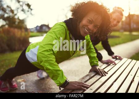 Two smiling sportswomen doing push-ups using bench in park - Stock Photo