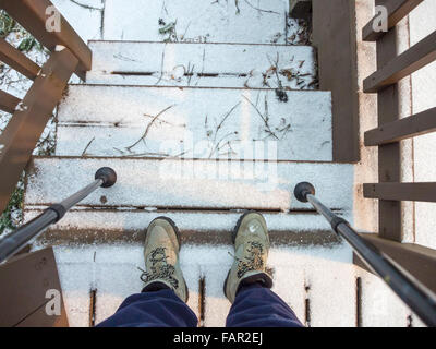 Wide angle view looking down at hiker's boots and poles on snow covered stair landing - Stock Photo