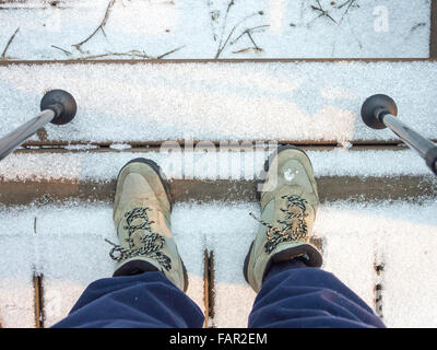 Hiker looking down at old worn boots standing on snow-covered stairs with poles - Stock Photo