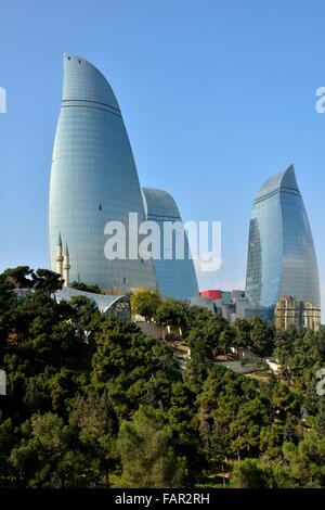 Looking up at the Flame Towers in Baku, capital of Azerbaijan, in the sunshine with trees in foreground. - Stock Photo