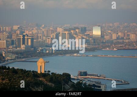 View over Baku, Azerbaijan, and the Caspian Sea, in sunshine with haze showing the 20th January monument in foreground. - Stock Photo