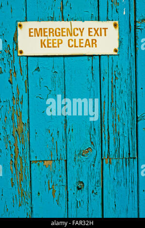 Emergency Exit sign on Blue Painted Door - Stock Photo