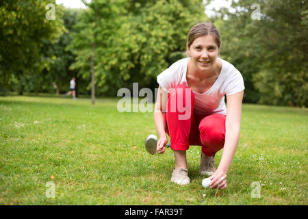 young golfer placing the golf ball on the tee - Stock Photo