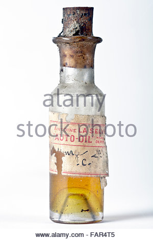 old little bottle with yellow liquid mentioning on the label auto oil - Stock Photo