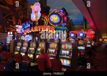 Elderly woman playing a slot machine in the casino of the Paris Hotel, Las Vegas, Nevada. - Stock Photo
