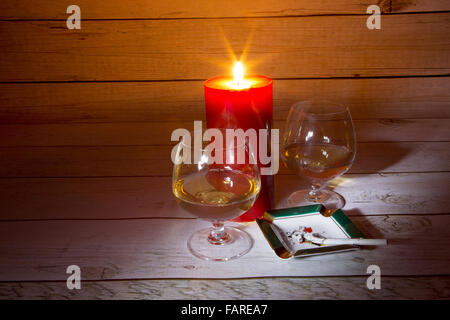 Two glasses of cognac, burning candles and burning cigarette in the ashtray in a romantic light on the background - Stock Photo