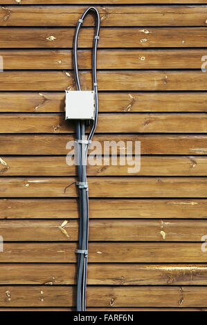 Fire dangerous electric white socket on a dry wooden wall of the rural house. Concept of ignoring of safety rules - Stock Photo