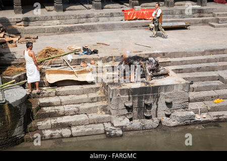 Hindu cremation ceremony at Pashupatinath Temple, a Hindu temple located on the banks of the Bagmati river. Kathmandu. - Stock Photo
