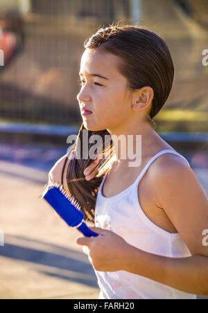 Young girl at the beach brushing her wet hair after swimming, St Kilda Beach, Melbourne Australia