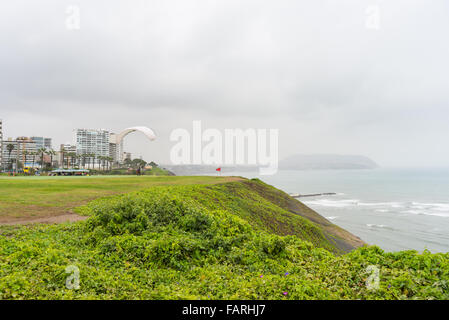 Paraglider launching from the coastline in Lima Miraflores, Peru. Winter season, cloudy and foggy sky, waving ocean. - Stock Photo
