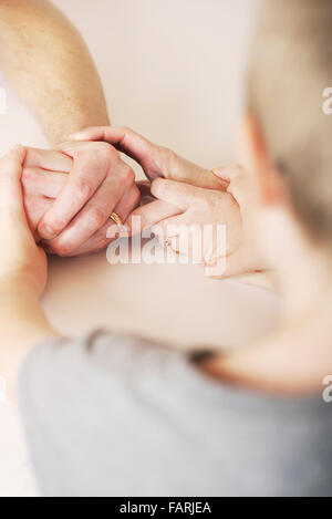 Child holds the hands of mother and father during a fragmented and strained relationship - Stock Photo