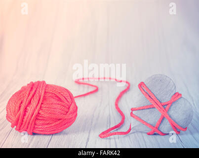 Wooden heart tied with red yarn, concept picture. - Stock Photo