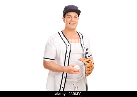 Young man in a baseball uniform holding a baseball and looking at the camera isolated on white background - Stock Photo