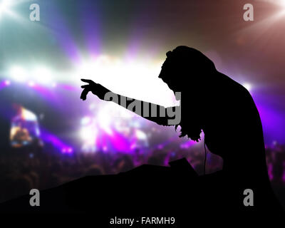 DJ with headphones at night club party under the spot lights and people crowd in background - Stock Photo