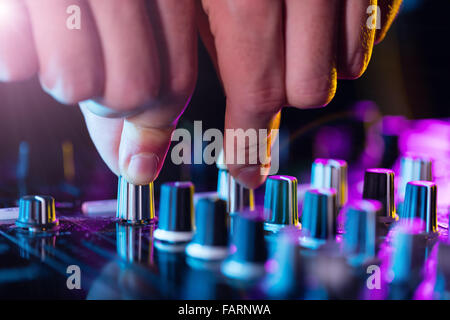 Detail of dj's hands operating on console - Stock Photo