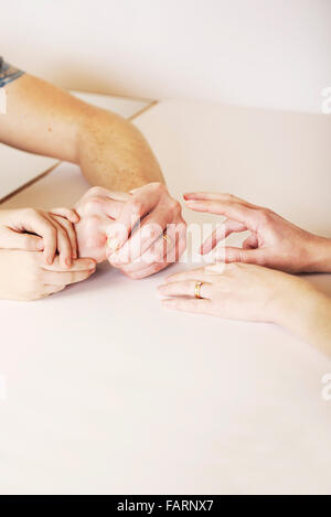 Child holds the hands of mother and father during a fragmented and strained relationship, bringing the family together - Stock Photo