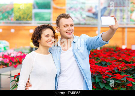 Young couple taking selfies at orangery. - Stock Photo