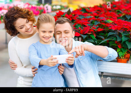 Young family taking selfies in the greenhouse - Stock Photo
