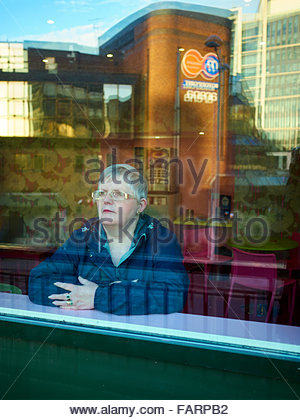 A woman with grey hair and wearing spectacles looking out of a cafe window and in deep thought - Stock Photo
