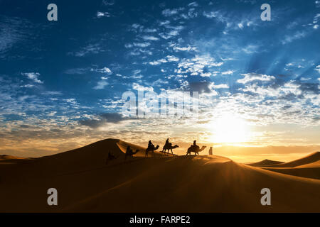 Caravan in the desert during sunrise against a beautiful cloudy sky. - Stock Photo