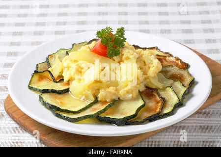 Roasted zucchini slices with potato and egg scramble - Stock Photo