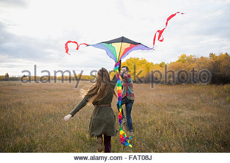 Couple flying a kite in autumn field - Stock Photo