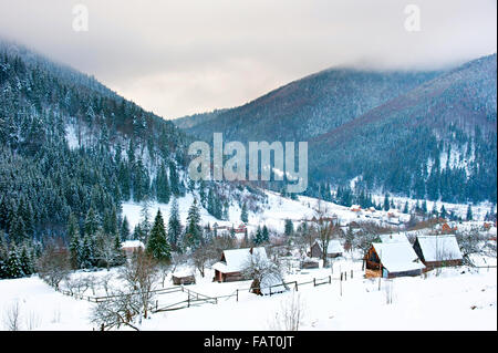 Transcarpathians village in the mountains covered by snow. Ukraine - Stock Photo