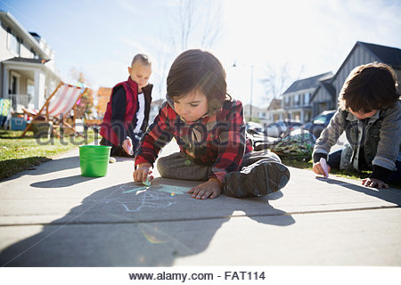 Kids drawing on sidewalk with chalk - Stock Photo