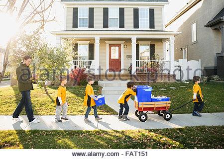 Coach and boys sports team gathering recycling neighborhood - Stock Photo