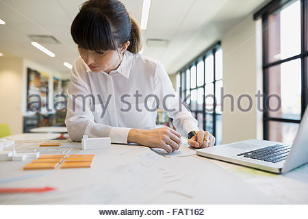 Focused architect examining models in office - Stock Photo