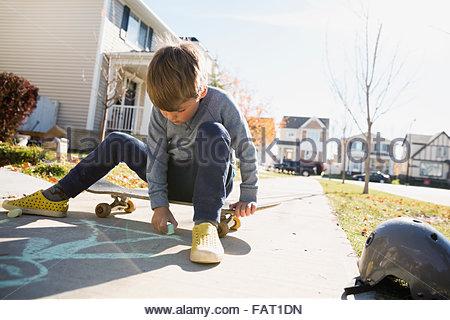 Boy on skateboard drawing on sidewalk with chalk - Stock Photo