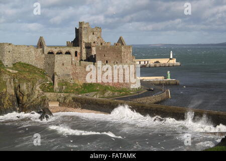 Peel Castle, Peel, Isle of Man with the bay and pier in the background. Waves crash on Fenella Beach, wall protects - Stock Photo