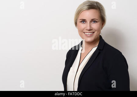 Attractive businesswoman with blond hair wearing a stylish jacket standing sideways looking at the camera with an - Stock Photo
