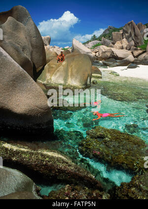 Tourists snorkeling in tide pools on La Digue Island in Seychelles - Stock Photo