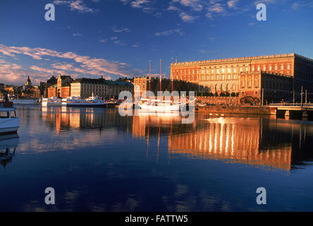 Boats anchored along Skeppsbron at sunrise with Royal Palace and Old Town in Stockholm - Stock Photo