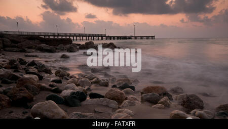 Seascape with jetty during a dramatic cloudy sunset  at Paphos area in Cyprus - Stock Photo