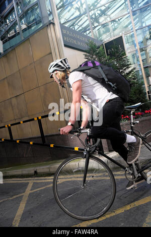 Male cyclist wearing helmet and rucksack courier office worker riding bike into basement of building near Broadgate - Stock Photo