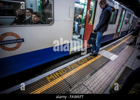 MIND THE GAP warning. London underground station with tube train and platform - Stock Photo