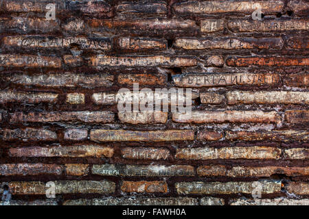 Names defacing a stone wall, Colosseum; Rome, Italy - Stock Photo