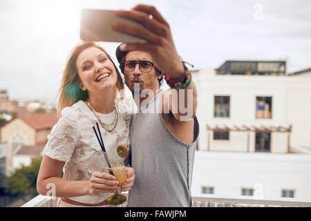 Two young friends taking a selfie on rooftop. Man holding smart phone and taking self portrait with woman holding - Stock Photo