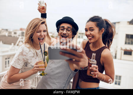 Small group of friends taking selfie on a mobile phone. Young man and women with drinks making funny face while - Stock Photo