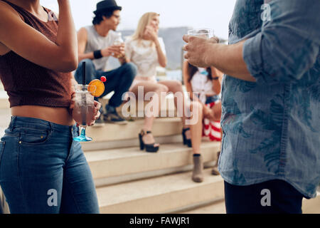 Cropped shot of a couple holding cocktails glasses while three people talking to each other in the background. Young - Stock Photo